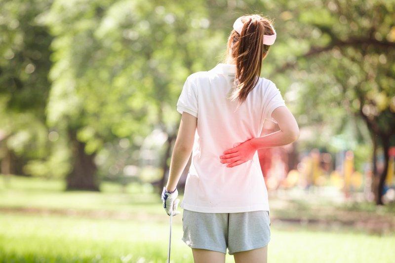 Dame mit Kreuzschmerzen auf dem Golfplatz